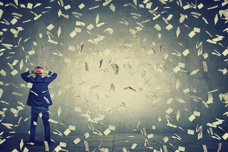 riches: Rear back view of business man standing in front of a wall under money rain dollar banknotes falling down, hands on head wondering what to do next. Full body length of businessman facing the wall