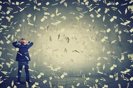Tylny widok z tyłu działalności człowieka stojącego przed ścianą pod dolarowych banknotów pieniądze deszcz pada, ręce na głowę zastanawiając się, co robić dalej. Pełna długość ciała biznesmen z widokiem na ścianę