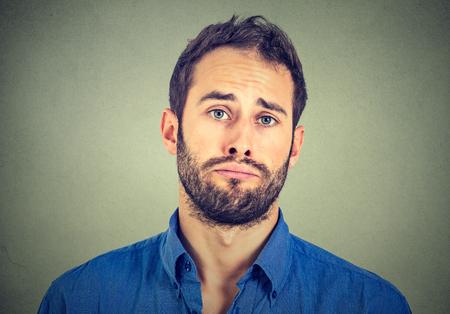 portrait triste jeune homme isolé sur gris fond mur
