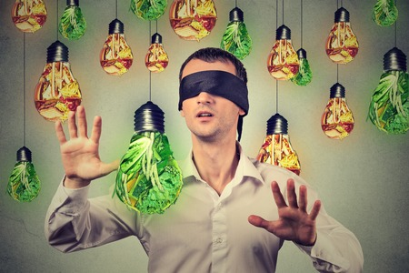 dietitian: Blindfolded young man walking through light bulbs shaped as junk food and green vegetables isolated on gray wall background. Diet choice right nutrition healthy lifestyle concept Stock Photo