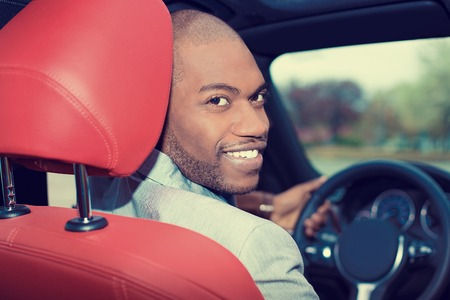 buy car: Portrait happy handsome young man in new car hands on wheel, turning around, smiling looking at, talking to passengers sitting in back seat. Driver license exam, test concept