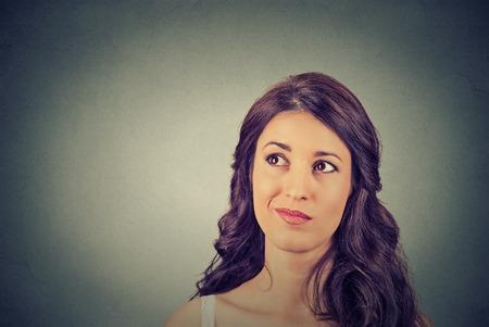 Primer divertido confundida mujer escéptica planificación pensando mirando hacia arriba aislados en el fondo gris de la pared copia espacio por encima de la cabeza. Humana emoción expresión sintiendo el lenguaje corporal, la percepción de reacción Foto de archivo