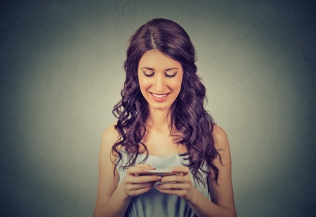 mobile marketing: Happy young woman holding using new smartphone connected browsing internet worldwide isolated on gray wall background. 4g data plan provider