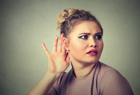secretly: Closeup portrait young nosy woman hand to ear gesture, trying carefully intently secretly listen in on juicy gossip conversation news isolated on gray wall background. Human face expression