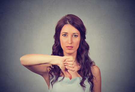 disapproval: Unhappy woman giving thumbs down gesture looking with negative expression and disapproval. Beautiful cute young woman on gray wall background. Stock Photo