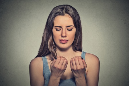 cravings: Worried woman looking at hands fingers nails obsessing about cleanliness isolated on grey background. Negative human emotion facial expression feeling perception Stock Photo