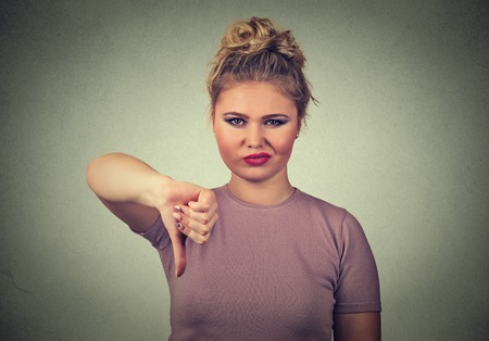 pissed off: Closeup portrait displeased angry pissed off woman annoyed giving thumbs down gesture looking with negative facial expression, disapproval, isolated on gray background. Human emotions attitude Stock Photo