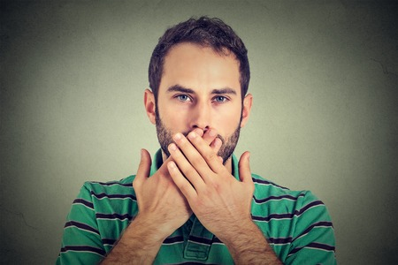 hand over: Closeup portrait man with hands over his mouth, speechless isolated on gray wall background