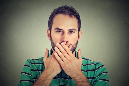 la boca: Retrato del primer hombre con las manos sobre su boca, sin palabras aisladas sobre fondo gris de la pared