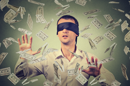 Blindfolded young businessman trying to catch dollar bills banknotes flying in the air isolated on gray wall background. Financial corporate success or crisis challenge concept