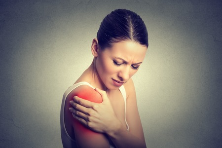Injured joint. Young woman patient in pain having painful shoulder colored in red. Medicine and health care concept. Gray background