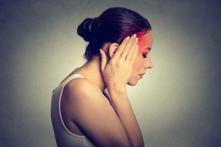 pain killers: Woman having headache with her head in her hands isolated on gray wall background