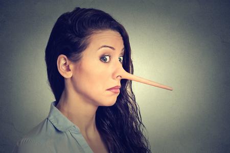 Frau mit dem langen Nase isoliert auf grau Wand Hintergrund. Lügner Konzept. Menschliches Gesicht Ausdrücke, Emotionen, Gefühle