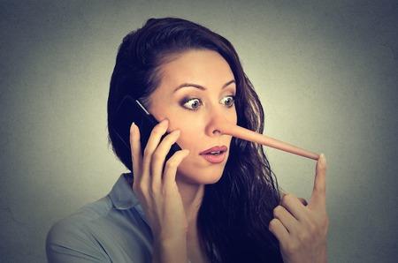 falso: Retrato sorprendió mujer con la nariz larga, hablando por teléfono móvil aislado en el fondo de la pared gris. concepto mentiroso. expresiones faciales humanas, emociones, sentimientos. Foto de archivo