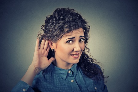 cochlear: Closeup portrait of unhappy hard of hearing woman placing hand on ear asking someone to speak up or listening to bad news isolated on gray background. Negative emotion facial expression Stock Photo