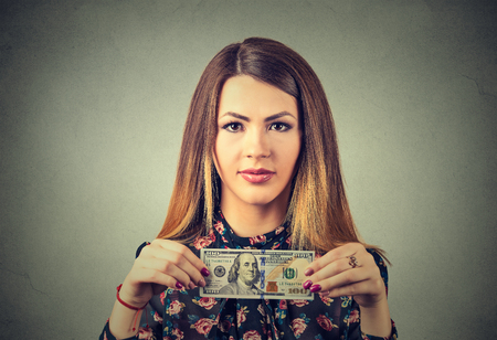 financial reward: Rich young woman with one hundred dollar bill isolated on gray wall background. Financial reward concept Stock Photo