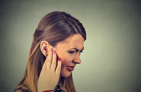 Tinnitus. Closeup side profile sick young woman having ear pain touching her painful head isolated on gray background