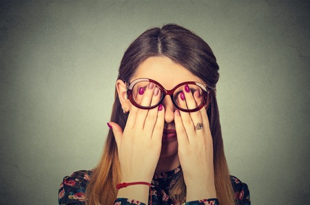 sightless: Closeup portrait young woman in glasses covering face eyes using her both hands isolated on gray wall background
