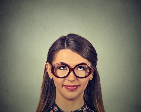 hispanic woman: closeup portrait headshot cute happy woman in glasses looking up isolated on gray wall background with copy space above head. Human face expressions, emotions