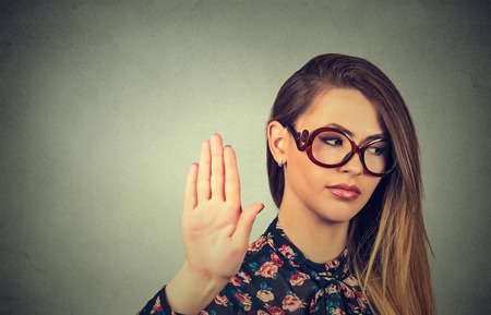 bad attitude: Closeup portrait young annoyed angry woman with bad attitude giving talk to hand gesture with palm outward isolated grey wall background. Negative human emotion face expression feeling body language