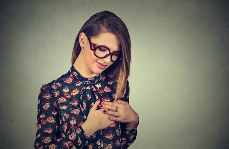 Mujer joven del retrato del primer con el dolor de pecho tocando el pecho aislado en el fondo de la pared gris