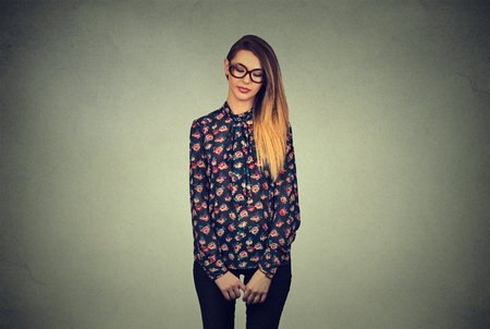 insecure: Sad shy insecure young woman in glasses looking down avoiding eye contact standing isolated on gray wall background