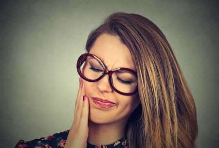 Closeup portrait young woman in glasses with sensitive toothache crown problem about to cry from pain touching outside mouth with hand isolated on gray background. Negative emotion face expression