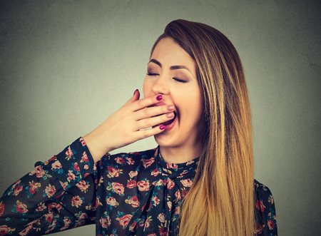 sleepiness: It is too early for meeting. Sleepy young woman with wide open mouth yawning eyes closed looking bored. Face expression body language Stock Photo