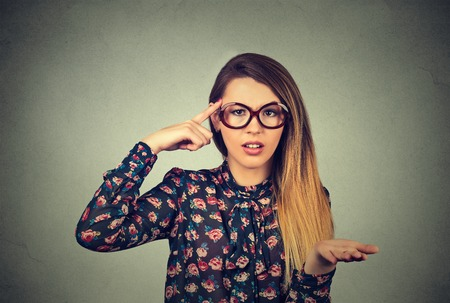 Closeup portrait of angry mad young woman gesturing with her finger against temple asking are you crazy? Isolated on gray wall background. Negative emotions facial expression body language reaction