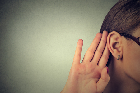personas escuchando: La mujer sostiene su mano cerca de la oreja y escucha cuidadosamente aislado en el fondo de la pared gris Foto de archivo