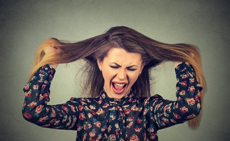 scold: Very angry woman pulling her hair out screaming Stock Photo