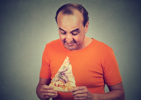 junks: Portrait of a middle aged man eating craving a pizza. Unhealthy eating diet nutrition concept