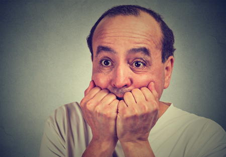 obsessive compulsive: Closeup portrait of scared middle aged guy biting his nails looking anxious in panic isolated on gray wall background. Human facial expression emotion feeling reaction
