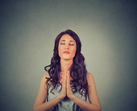 kneeling woman: Closeup portrait of a young woman praying eyes closed isolated on gray wall background Stock Photo