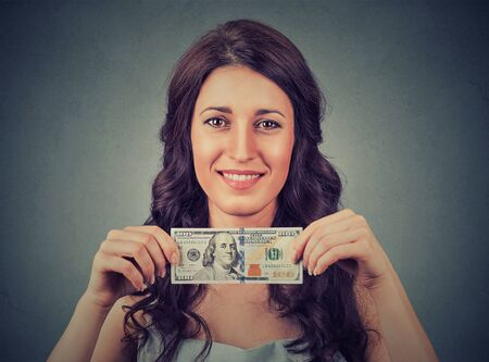 one hundred dollar bill: Happy young business woman holding money one hundred dollar bill isolated on gray wall background