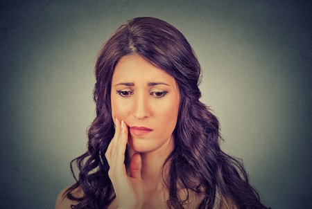 amalgam: Closeup portrait young woman with sensitive toothache crown problem about to cry from pain touching outside mouth with hand isolated on gray background. Negative human emotion face expression feeling