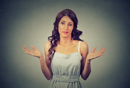 ambiguous: Portrait dumb looking woman arms out shrugs shoulders who cares so what I dont know isolated on gray wall background. Negative human emotion, facial expression body language life perception attitude Stock Photo