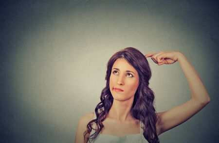 negative: Closeup portrait young woman scratching head, thinking daydreaming deeply about something looking up isolated on gray wall background. Human facial expressions, emotions, feelings, signs, symbols