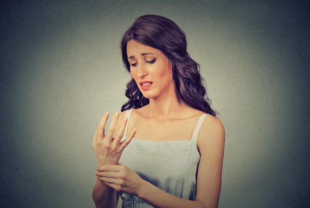 carpal: Young woman holding her painful wrist isolated on gray wall background. Negative face expression