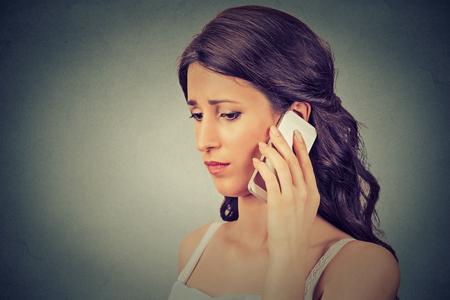 preocupacion: Mujer joven en cuestión hablando por teléfono móvil