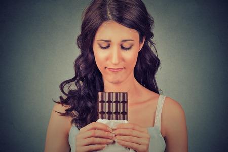 malos habitos: Retrato triste mujer joven cansada de restricciones en la dieta que anhelan dulces de chocolate aislados sobre fondo gris de la pared. Emoción expresión humana. Concepto de nutrición. Sentimientos de culpa Foto de archivo