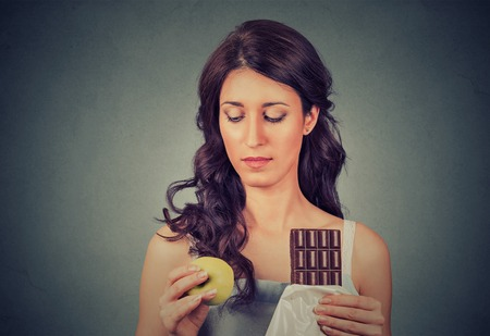 cravings: Confused looking woman with chocolate and apple trying to make a healthy choice control her body weight isolated on gray wall background. Human face expression. Dieting  concept