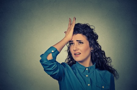 duh: Regrets wrong doing. Closeup portrait silly young woman, slapping hand on head having duh moment isolated on gray background. Negative human emotion facial expression feeling, body language, reaction