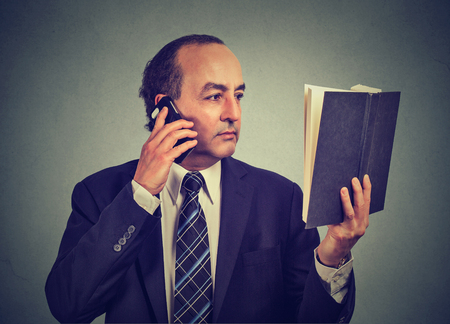 wallstreet: Closeup portrait serious middle aged business man in suit, executive reading book talking on smart phone isolated on gray wall background. Human face expression, emotion. Stock Photo