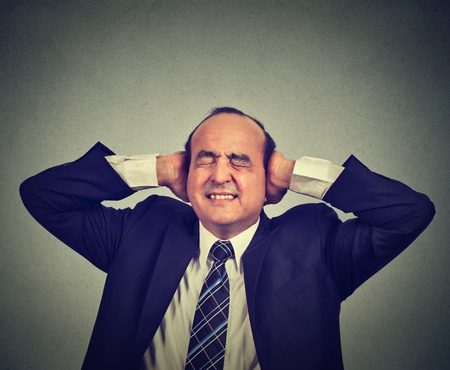 too many: Stressed man upset frustrated has too many thoughts headache isolated on gray wall background