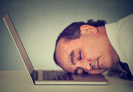deprived: Side profile businessman sleeping on a laptop at his desk, tired middle aged guy employee isolated on grey office wall background. Sleep deprivation, long working hours concept Stock Photo