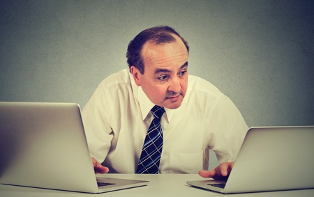 business media: Middle aged business man multitasking working on two computers in his office Stock Photo
