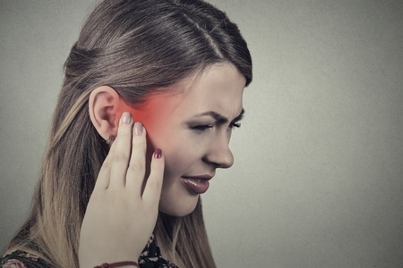 dolor de oido: Tinnitus. Closeup side profile sick young woman having ear pain touching her painful head temple colored in red isolated on gray background Foto de archivo
