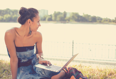 teleworker: Girl with laptop. Beautiful young woman with notebook sitting on the grass. Outdoor. Sunny day. Back to school