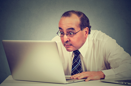 Portrait middle aged shocked business man sitting in front of laptop computer looking at screen isolated on gray wall background. Funny face expression emotion feelings problem perception reaction Stock Photo